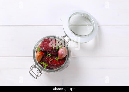 jar of baked beetroot with garlic and thyme on white wooden background - Stock Photo