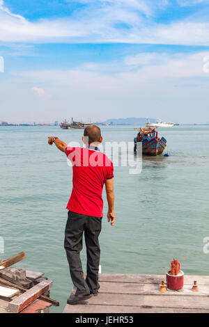 GEORGE TOWN, MALAYSIA - MARCH 27: Malaysian man shows something in the water on March 27, 2016 in George Town, Malaysia. - Stock Photo