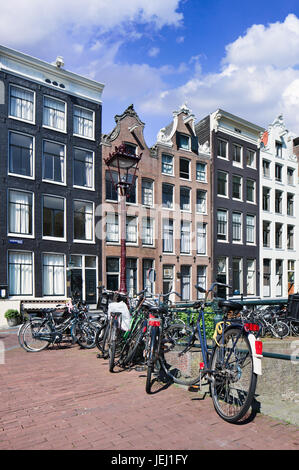 Bicycles parked against a rail with renovated ancient mansions on the background, Amsterdam, The Netherlands. - Stock Photo