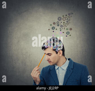 Successful businessman thinking and creating  with a pencil pointed to his head a coloruful brain made from gear - Stock Photo