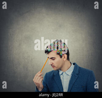 Creativity concept of a businessman pointing with a pencil to his head with a colorulful brain made from gears over - Stock Photo