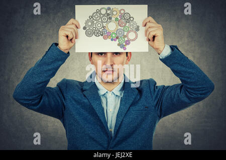 Stressed young man holding a white paper over his head with a brain losing his color, isolated on grey wall background.Young - Stock Photo