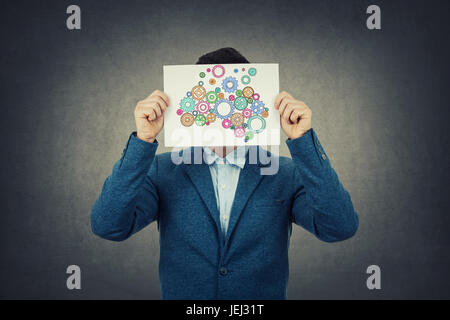 Businessman covering his face using a paper with brain made from gear sketch forming a complet coloruful brain.Finding - Stock Photo