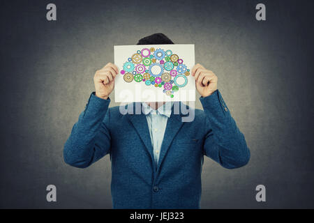 Creativity concept of a businessman covering head with a colorulful brain made from gears over his head.Idea concept. - Stock Photo