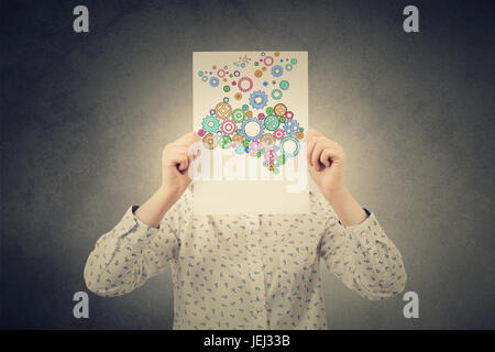 Young Student,Businesswoman covering his face with a empty white paper with a colorulful brain made from gears over - Stock Photo
