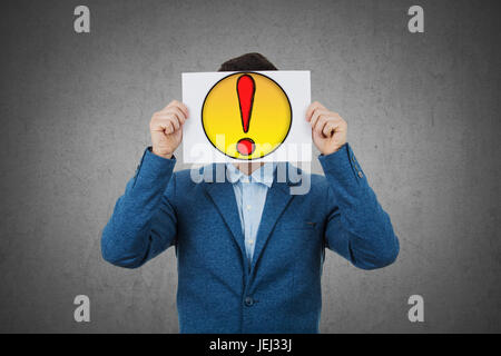 Businessman covering his face using a white paper with drawn question mark, like a mask, for hiding his identity. - Stock Photo