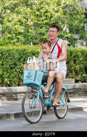 BEIJING-AUGUST 14, 2016. Man with his son on a rental bike at Houhai area. It is very popular among foreign tourists - Stock Photo