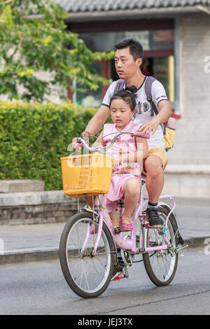 BEIJING-AUGUST 14, 2016. Man with his daughter on a rental bike at Houhai area. It is very popular among foreign - Stock Photo