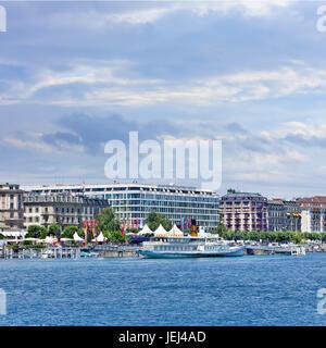 GENEVA-JULY 25, 2011. Anchored white cruise boat in front of luxurious hotels at Geneva Lake shore. Geneva has over - Stock Photo