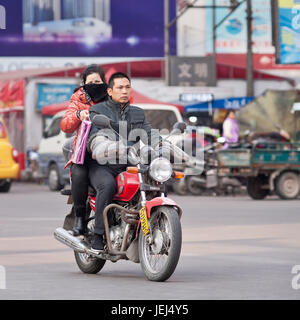 HENGDIAN-DEC. 29, 2014. Couple on Yamaha motorcycle. Chinese buy 16 million bikes a year. Domestic manufacturers - Stock Photo