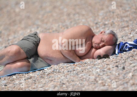 A large gentleman laying shirtless in the sun on a beach in Summer in the UK. - Stock Photo