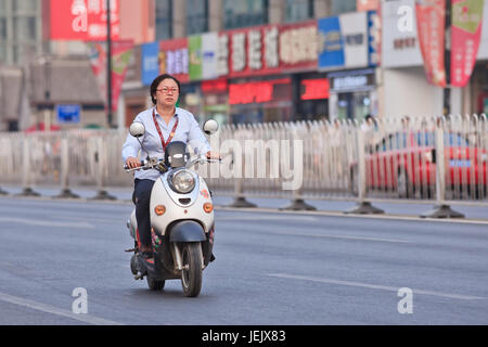 BEIJING-JULY 10, 2015. Woman on an e-bike. In a decade, e-bikes in China climbed from near zero to over 150 million - Stock Photo