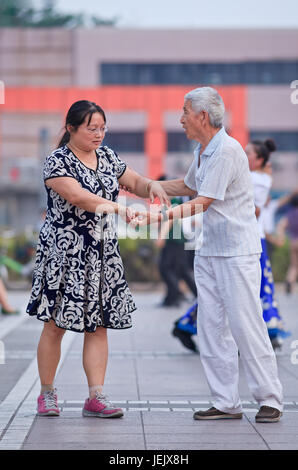 BEIJING-JULY 10, 2015. Collective square dancing is a very popular phenomenon in China and for many people a sort - Stock Photo