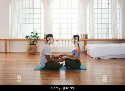Side view of beautiful young couple doing yoga at home. They are sitting together on the yoga mat holding hands. - Stock Photo