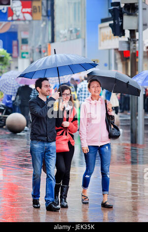 Caucasian couple and Chinese girl with umbrella in city center. Shanghai has humid subtropical climate, summer is - Stock Photo
