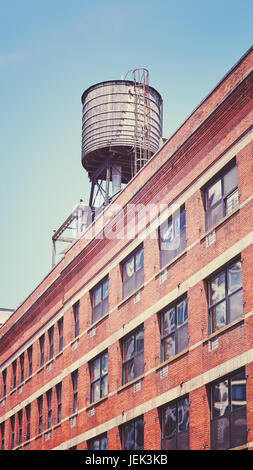 Vintage toned picture of a rooftop water tank on a New York city apartment building, USA. - Stock Photo