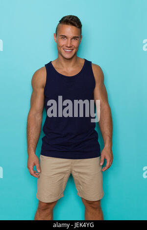 Handsome young man in blue tank top and beige shorts, standing relaxed, looking at camera and smiling. Three quarter - Stock Photo