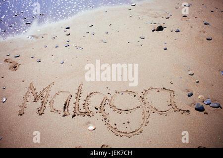 malaga handwritten in the sand with a shelfish - Stock Photo