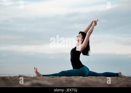Girl practicing yoga in nature hanumanasana monkey pose. - Stock Photo