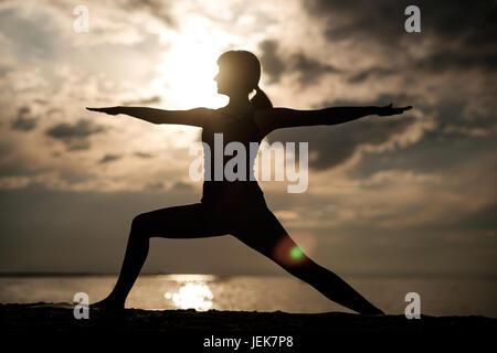 Sporty fit caucasian woman doing asana Virabhadrasana 2 Warrior pose posture in nature. - Stock Photo