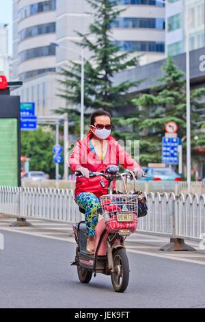 KUNMING-JUNE 30, 2014. Woman on an e-bike. An estimated 200 million Chinese now use e-bikes, 1,000-fold increase - Stock Photo