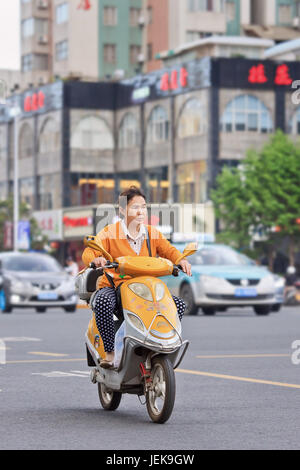 KUNMING-JUNE 30, 2014. Woman on yellow electric bike. Many electric bikes in China are the scooter style e-bike - Stock Photo