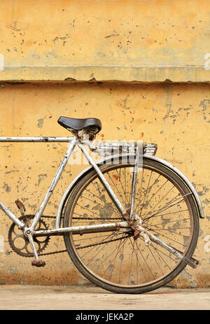 Rusty Chinese bike against weathered yellow wall - Stock Photo