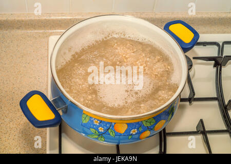 Cooking pearl barley in pot on gas stove - Stock Photo