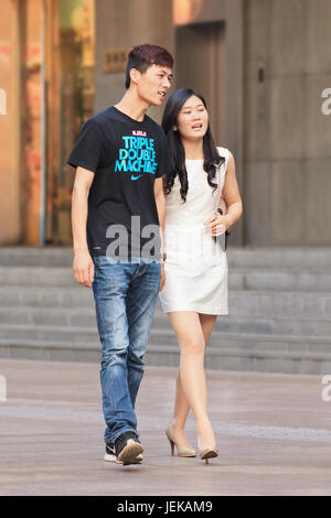 Couple walking in shopping area. China's Marriage Law of 1980 went into effect in 1981, it permits women and  to - Stock Photo