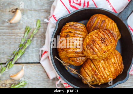 Baked potatoes with rosemary in a cast-iron frying pan. - Stock Photo