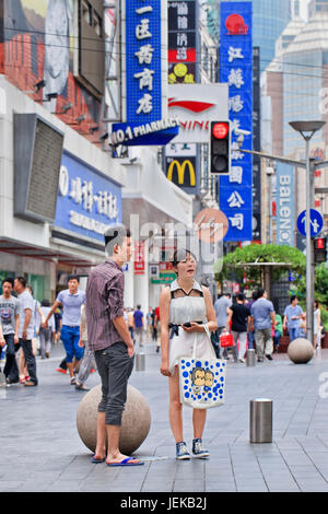 Young Chinese couple in Nanjing East Road. It is China's 3.4-mile long premier shopping street, a must-see metropolitan - Stock Photo