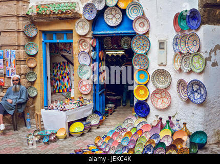 Man outside his shop selling traditional souvenirs in the souks of the old medina, Essaouira - Stock Photo