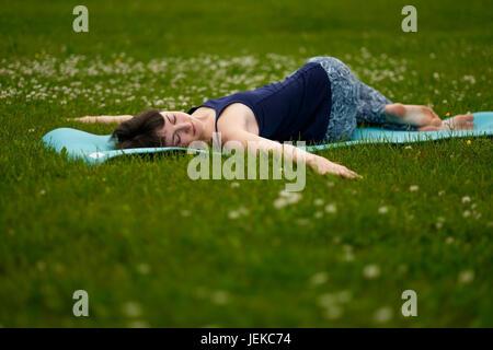 Beautiful caucaisan young woman working out outdoors on blue mat. Jathara Parivartanasana top view - Stock Photo