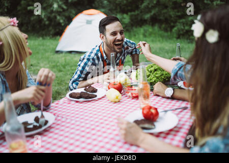 Cheerful friends sitting at table and having meal in nature - Stock Photo