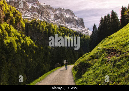 Man walking along mountain road, Seealpsee, Appenzell Innerrhoden, Switzerland - Stock Photo