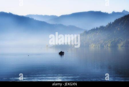 Man in rowing boat on lake Aegeri, Zug, Switzerland - Stock Photo