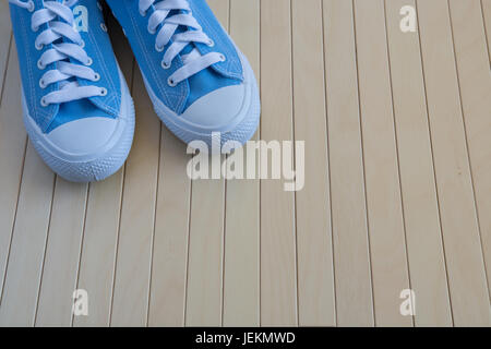 Pair of blue sneakers on the wooden background - Stock Photo