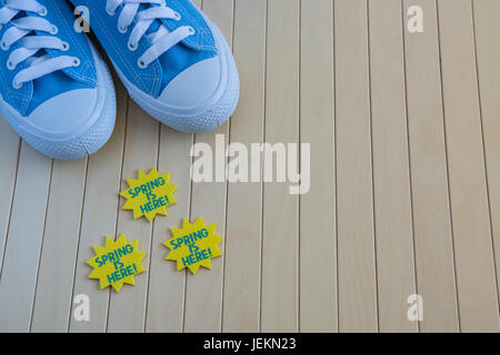 Blue sneakers with spring signs on the wooden background - Stock Photo