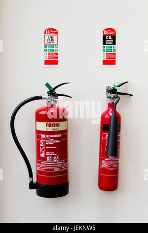 Foam and CO2 Fire extinguishers with identity wall cards and security seals, in  easy to access fire exit route - Stock Photo
