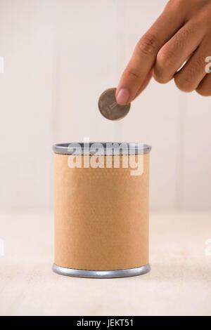 Putting money into donation box. Donate concept. - Stock Photo