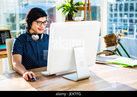 Smiling asian businessman using computer - Stock Photo
