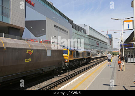 A goods train passes through the newly constructed Shepherds Bush station, next to the Westfield Shopping centre - Stock Photo