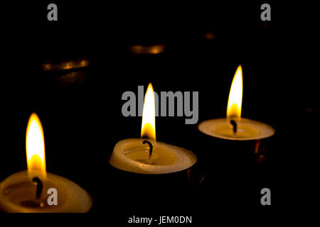 Lit tea candles burning in a dark room. - Stock Photo