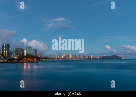 A skyline view of Diamond Head and Ala Moana at dusk. - Stock Photo