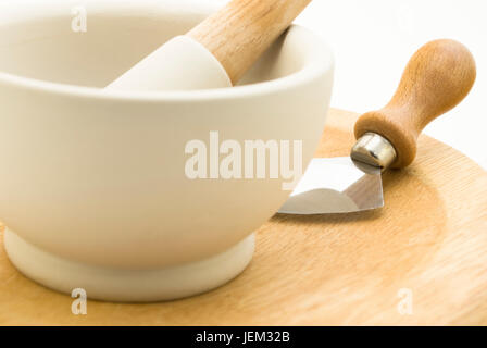 Close up of a cream stone pestle and mortar standing on a wooden mezzaluna chopping board with blade.  White background. - Stock Photo