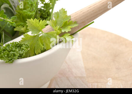 Closeup of a selection of herbs in a cream coloured mortar with pestle on worn wooden chopping board.  Subject cuts - Stock Photo