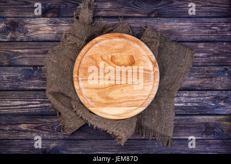 Round tray for pizza on dark wooden table. Cutting board on rustic background. Top view. Copy space. - Stock Photo