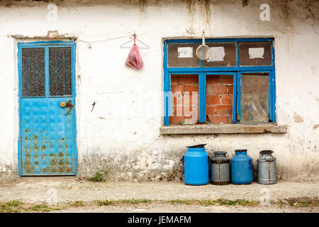 old milk jugs in a row in front of an abandoned house - Stock Photo