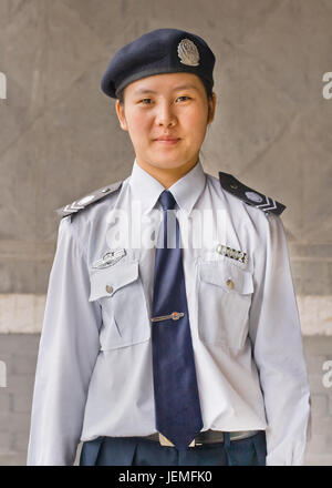 BEIJING-SEPTEMBER 28, 2012. Young female Police officer dressed in a uniform poses in front of a wall. - Stock Photo