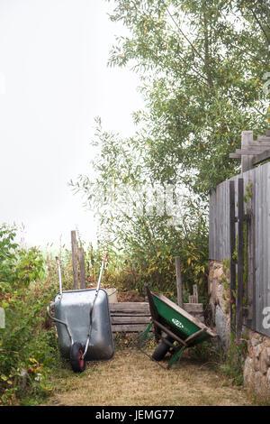 Wheelbarrows in garden - Stock Photo